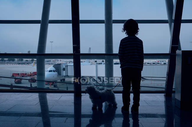 Anonymous boy with dog in airport — Stock Photo
