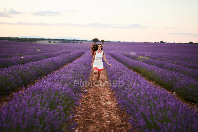 Young woman in dress running between violet lavender field — Stock Photo