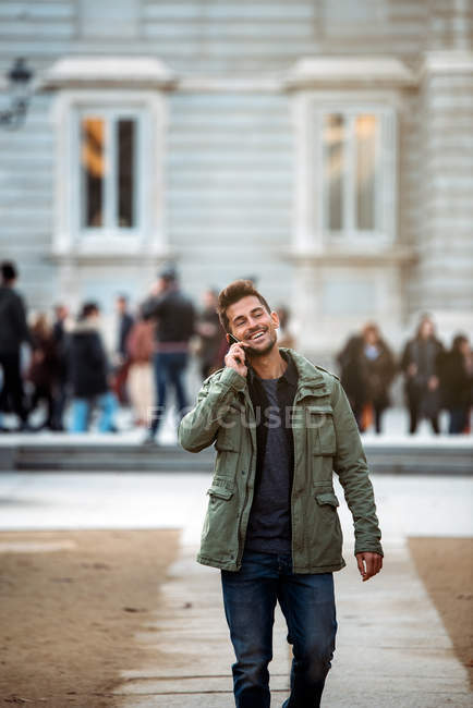 Young man on the mobile phone and walking in madrid during winter — Stock Photo
