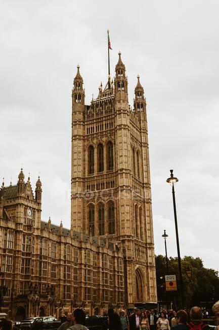LONDRES, REINO UNIDO - OUTUBRO 23, 2018: Multidão de turistas caminhando perto da fachada do majestoso Palácio de Westminster, em Londres, Inglaterra — Fotografia de Stock