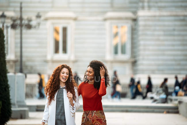 Two cheerful young women walking in the streets of Madrid on winter — Stock Photo
