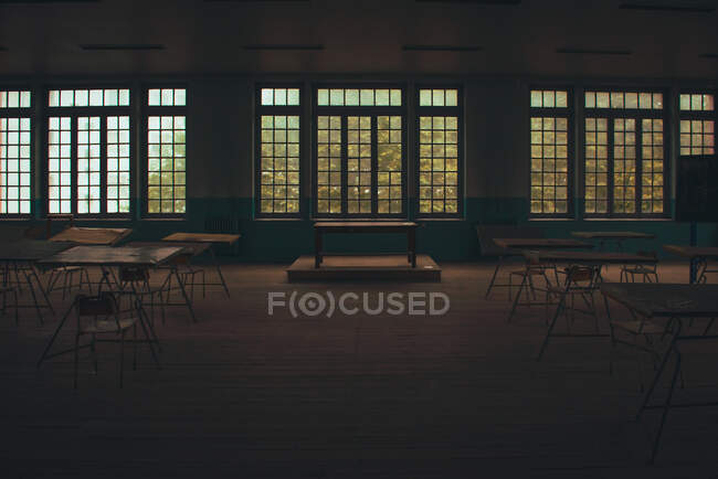 Composition of wooden tables in empty room near big windows — Stock Photo