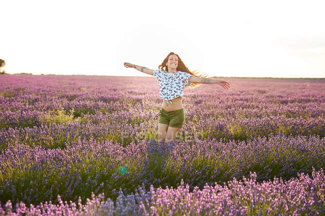 Mujer joven girando con los brazos extendidos entre el campo de lavanda violeta - foto de stock
