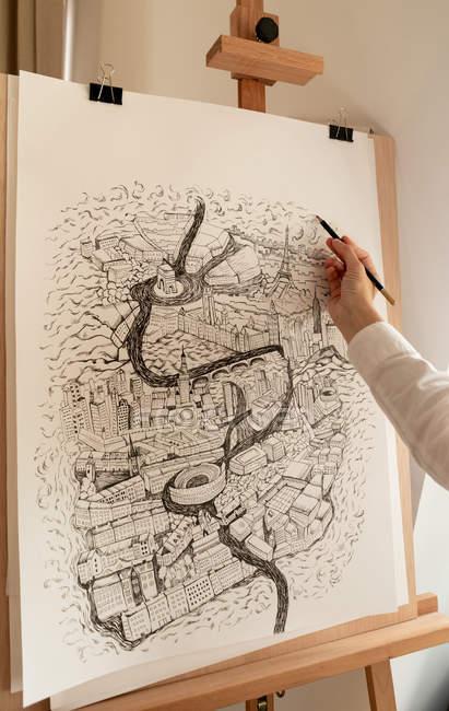 Mujer con lápiz pintando ciudad sobre papel grande - foto de stock