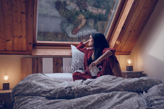 Sensual female with mug sitting on bed — Stock Photo