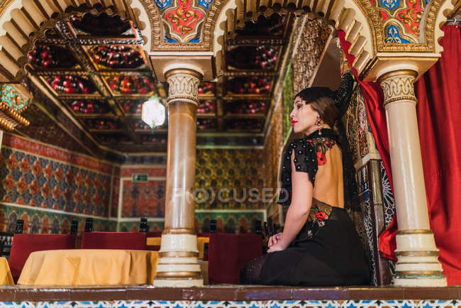 Side view of passionate young woman in dress sitting near table with chairs in luxury room of cafe decorated by mosaic — Stock Photo