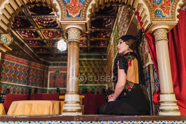 Vista lateral da jovem apaixonada em vestido sentado perto da mesa com cadeiras em sala de luxo de café decorado por mosaico — Fotografia de Stock