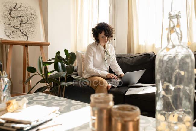 Mujer usando el ordenador portátil cerca dibuja en los papeles en el sofá en la habitación - foto de stock