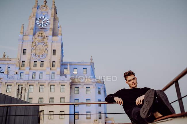 Hombre guapo en el techo cerca de edificios antiguos y gran pancarta - foto de stock