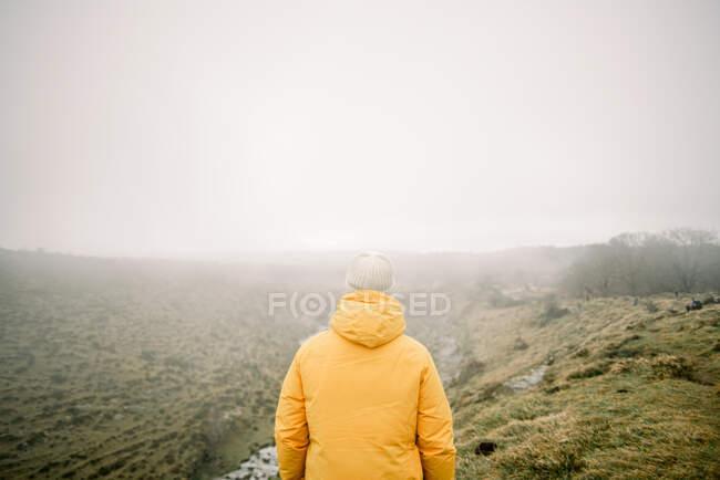 Человек стоит на холме — стоковое фото