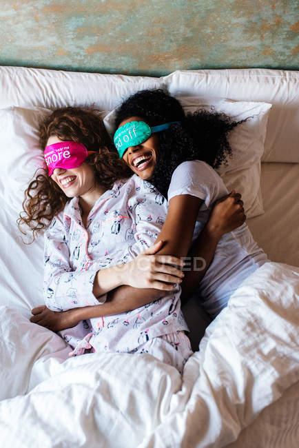 Zwei Mädchen schlafen entspannt im Bett mit Augenbinde zu Hause lächelnd — Stockfoto