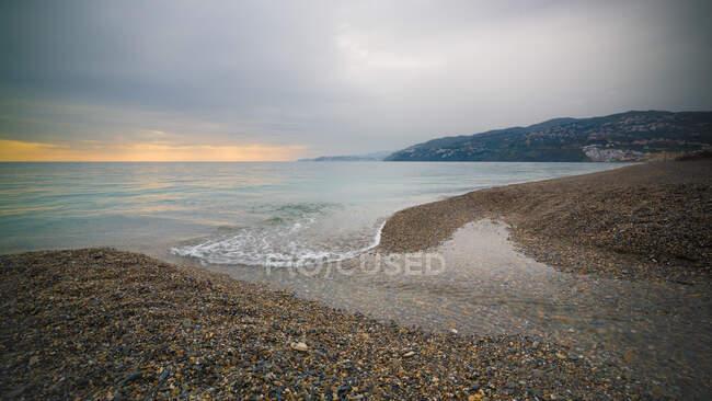 Incroyable côte rocheuse de mer calme pendant magnifique coucher de soleil — Photo de stock