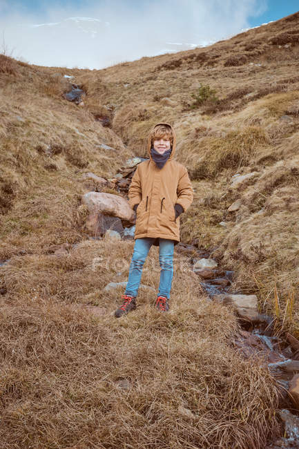 Cute boy standing on hill near brook — Stock Photo