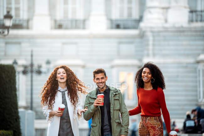 Três jovens amigos caminhando e bebendo café nas ruas de Madrid no inverno — Fotografia de Stock