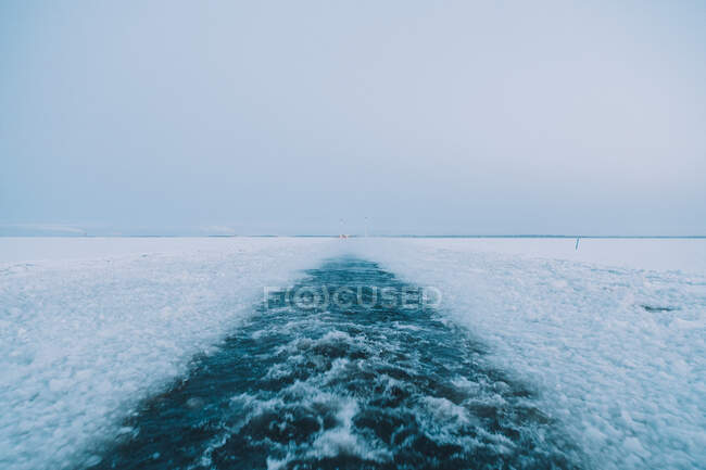 Cold water of Arctic sea splashing near pieces of broken ice on gray day — Stock Photo