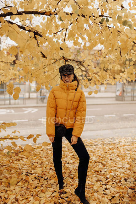 Portrait of smiling young woman in stylish warm clothes standing on autumn street — Stock Photo