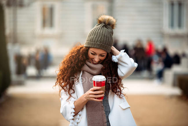 Cheerful woman drinking coffee wandering in the streets of Madrid on winter — стокове фото