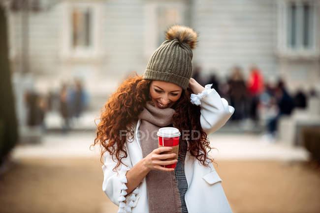 Веселая женщина пьет кофе на улицах Мадрида зимой — стоковое фото