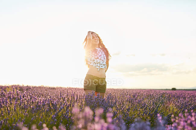 Woman standing between big violet lavender field at sunset — стокове фото