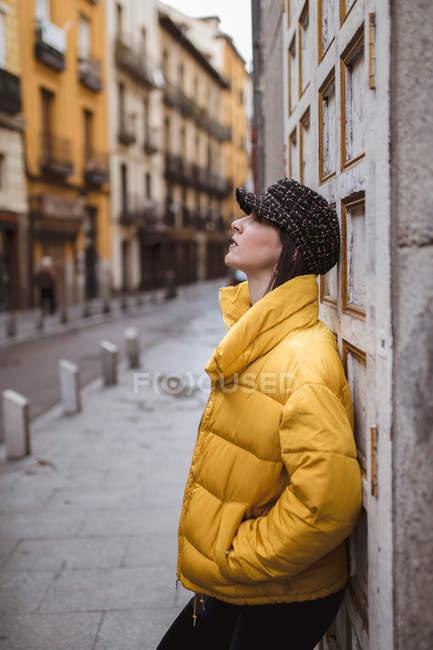 Мечтательная молодая женщина в модном наряде, опирающаяся на выветрившуюся стену на городской улице — стоковое фото