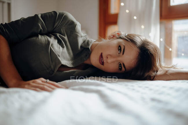 Beautiful young female in stylish outfit smiling and looking at camera while lying on comfortable bed in cozy room — Stock Photo