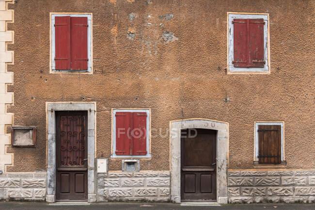 Старий будинок з червоними вікнами і коричневими дверима в Піренеях. — стокове фото