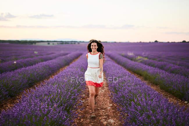 Mujer joven corriendo entre filas de campo de lavanda violeta - foto de stock