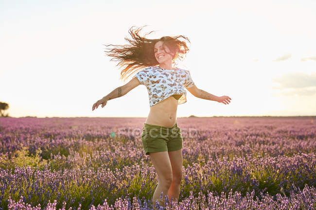 Smiling young woman whirling in big violet lavender field — Stock Photo