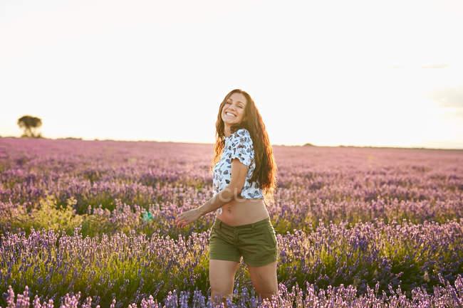 Улыбающаяся молодая женщина кружится в большом фиолетовом лавандовом поле — стоковое фото
