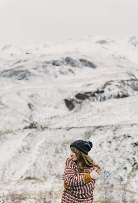 Attractive young lady in sweater and hat with crossed hands near hill on blurred background in Pyrenees — Stock Photo