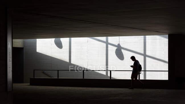 Silhouette di giovane ragazzo con smartphone di navigazione zaino mentre in piedi vicino alle scale all'interno di un edificio moderno — Foto stock