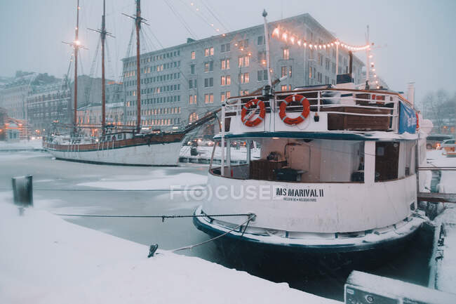 Modern ship standing near pier in icy port of brightly illuminated Arctic city at night — Stock Photo