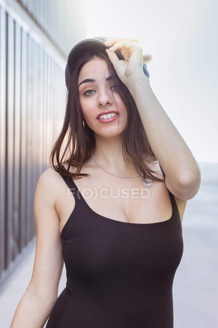 Appassionato giovane donna in Tank Top tenendo tappo sulla testa e guardando fotocamera su sfondo sfocato — Foto stock