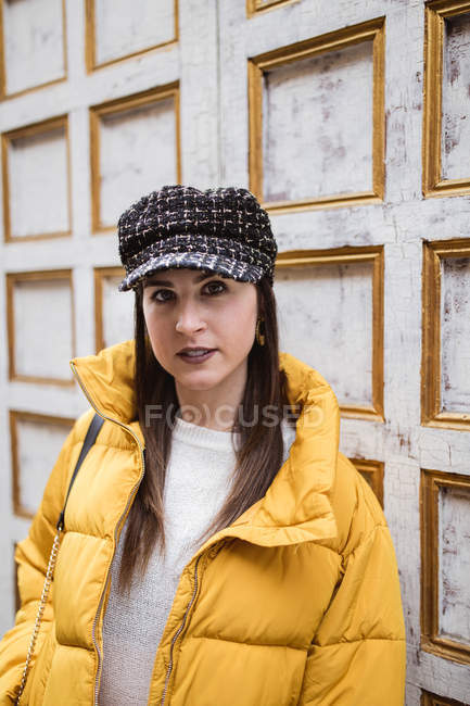 Portrait of young woman in trendy outfit while standing near weathered wall on city street — Stock Photo