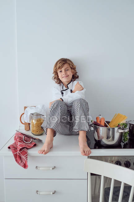 Funny little cook sitting near saucepans with vegetables on electric cooker in modern light kitchen — Stock Photo