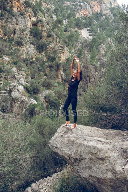 Atractiva hembra en traje casual sonriendo con los brazos en el borde de piedra áspera cerca de una montaña maravillosa en el hermoso parque - foto de stock