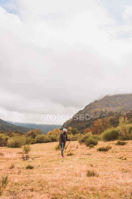 Vue latérale de dame en chapeau et veste de ski avec sac à dos et bâton de marche marchant sur la prairie près de la montagne dans les nuages à Isoba, Castille et Léon, Espagne — Photo de stock