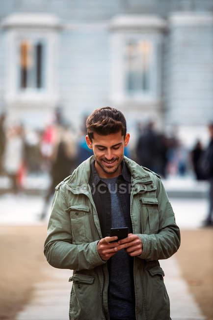 Молодой человек по мобильному телефону и прогулки в Мадриде в течение зимы — стоковое фото