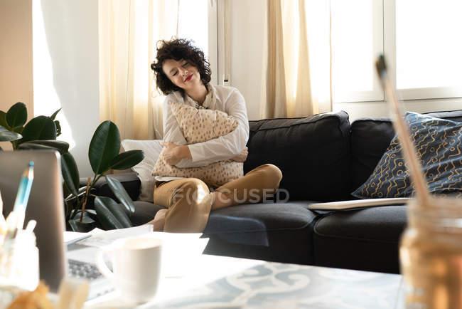 Giovane donna felice con gli occhi chiusi seduto sul divano vicino al tavolo basso con spazzole in lattina e laptop in stanza luce — Foto stock