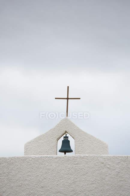Простий хрест і невеликий Белл на вершині білий церковна будівля проти хмарного неба — стокове фото