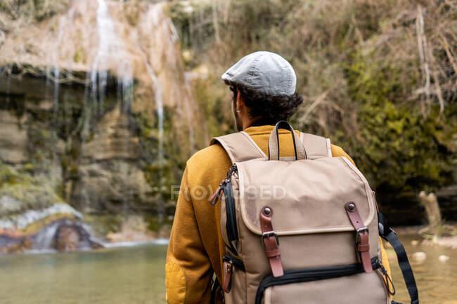 Погляд на подорожнього чоловіка з протягнутими руками, що стоять на каміннях і захоплюються фантастичним водоспадом в лісі в Іспанії. — стокове фото