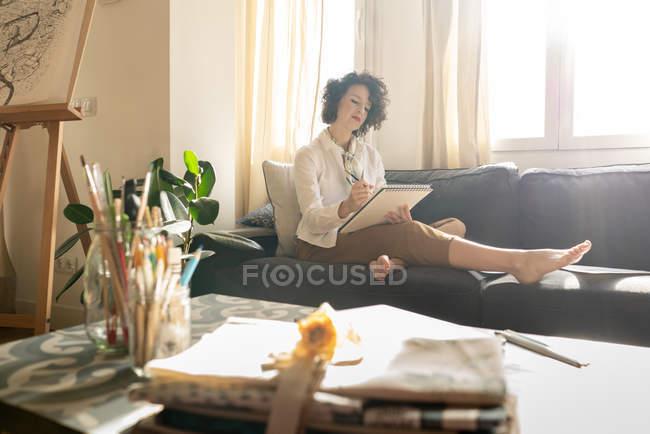 Жінка малює на папері на дивані в кімнаті. — стокове фото