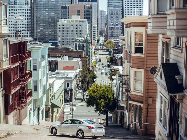 Conducción de automóviles en la calle entre edificios y rascacielos en el día de verano en San Francisco, Estados Unidos - foto de stock