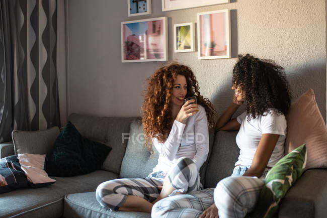 Young cheerful women friends seating relaxed on the sofa at home in pajamas talking to each other - foto de stock