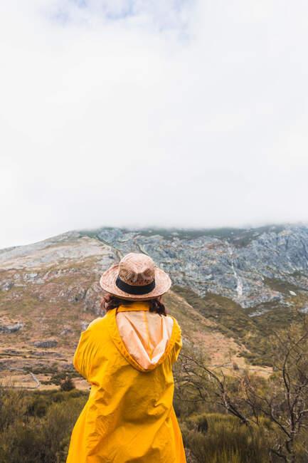 Rückenansicht einer Dame mit Hut und gelbem Regenmantel mit Blick auf die Landschaft in Isoba, Kastilien und León, Spanien — Stockfoto