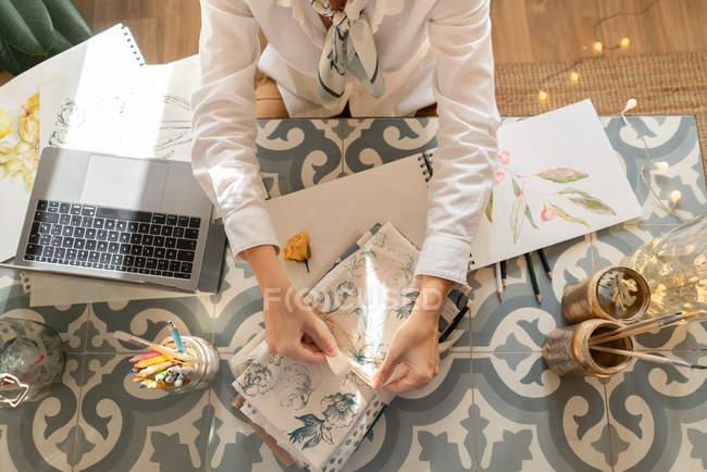 Zugeschnittenes Bild einer Frau am Tisch mit Laptop, Pinseln, Materialien, Bleistiften und Laken im Zimmer — Stockfoto