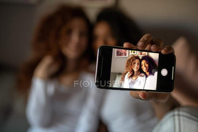Jeunes femmes gaies amis assis détendus sur le canapé avec téléphone mobile prenant un selfie — Photo de stock