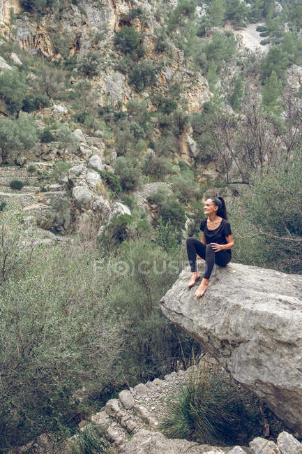 Attractive female in casual outfit sitting in edge of rough stone near wonderful mountain in beautiful park — Stock Photo