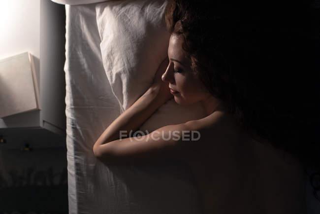 Вид сзади на обнаженную женщину, лежащую в постели ночью — стоковое фото