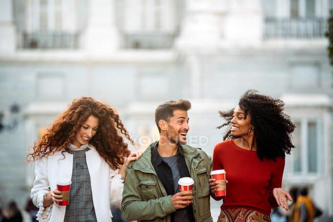 Трое молодых друзей гуляют и пьют кофе на улицах Мадрида зимой — стоковое фото